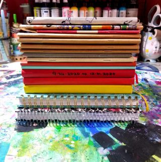 A pile of journals with various colored bindings and various shapes and sizes.