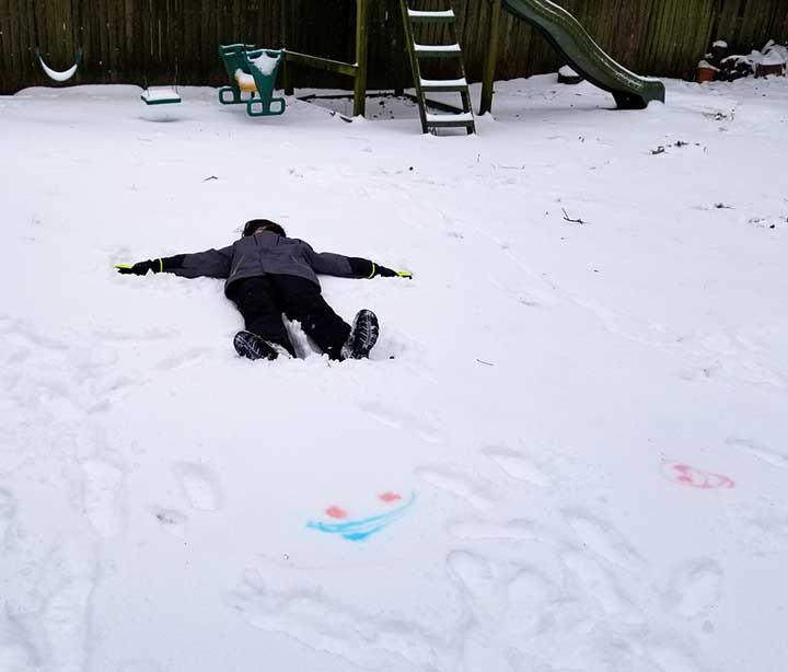 Photo of a child laying in the snow making a snow angel.